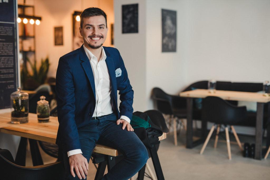 na zdjęciu znajduje się uśmiechnięty mężczyzna w garniturze siedzący na stole